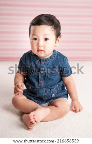 Cute funny baby in a jeans dress on a pink background