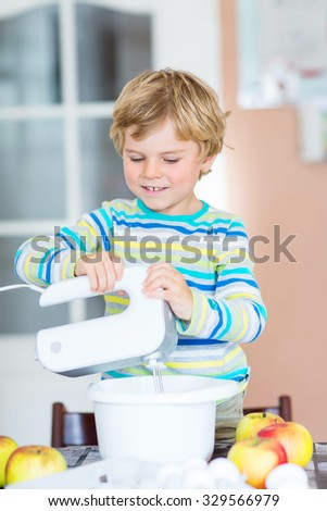 Cute funny blond kid boy of 3 years baking apple cake in domestic kitchen. Happy child having fun with working with mixer, flour, eggs and fruits.