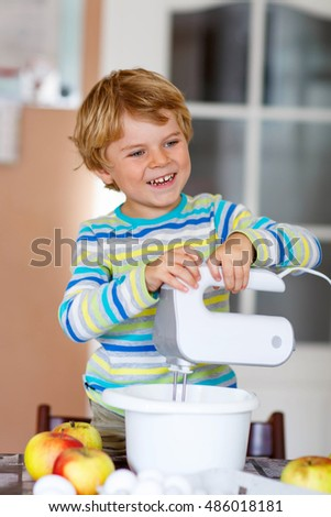 Cute funny blond preschool kid boy baking apple cake and muffins in domestic kitchen. Happy child having fun with working with mixer, flour, eggs and fruits at home.
