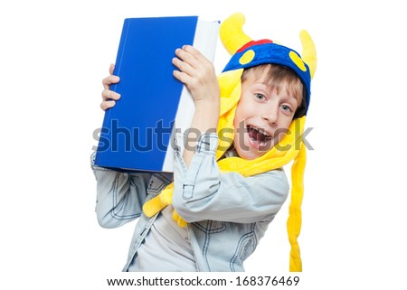 Cute funny boy in a funny hat holding a very big blue book above looking crazy (isolated on white background) - stock photo