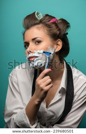 Cute funny  brunette woman in hair curlers wearing men shirt and tie undone posing with foam on face, isolated on blue background, role gender reversal concept - stock photo