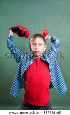 Cute funny child with boxer glove and holding a dumbbell looking strong and tough  - stock photo