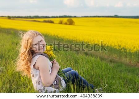 Cute funny girl on rape field - stock photo