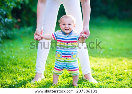 Cute funny happy baby in a colorful shirt making his first steps on a green lawn in a sunny summer garden, mother holding his hands supporting by learning to walk - stock photo