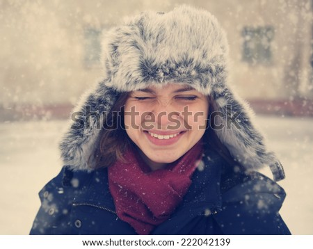 cute funny happy  girl in a fur cap  laughing under the snow, image with instagram retro effect - stock photo