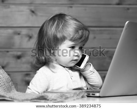 Cute funny little baby boy with long blonde curly hair speaking by mobile phone near computer indoor on wooden background, horizontal picture