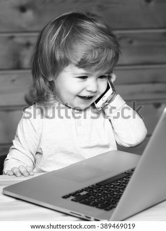 Cute funny little baby boy with long blonde curly hair speaking by mobile phone near computer indoor on wooden background, vertical picture - stock photo