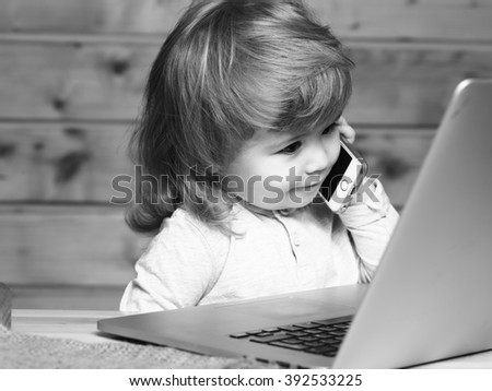 Cute funny little baby boy with long blonde curly hair speaking by mobile phone near computer indoor on wooden background, horizontal picture - stock photo