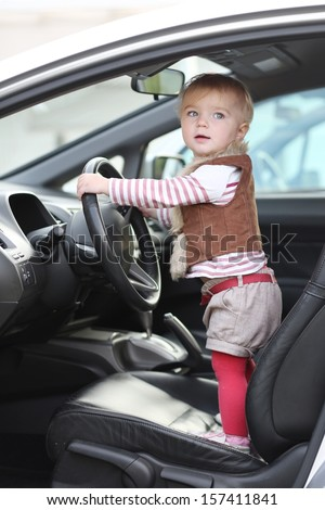 Cute funny little baby girl stands inside of the car on driver seat holding steering wheel - stock photo