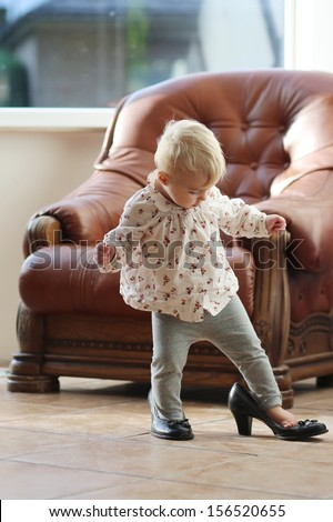Cute funny little baby girl walks at home trying mom's black high heel shoes - stock photo