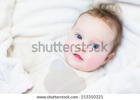 Cute funny little baby wearing a warm knitted sweater relaxing in a stroller on a white blanket - stock photo