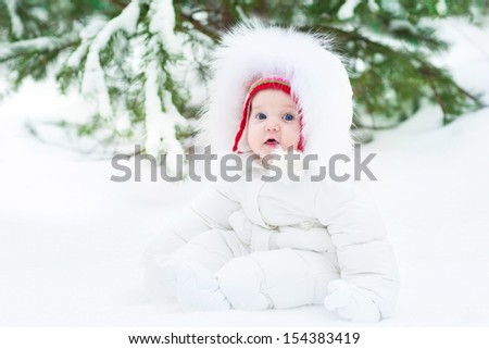 Cute funny little baby wearing a warm white winter jacket and a red hat sitting under a christmas tree in snow - stock photo