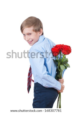 Cute funny little boy hiding a bouquet of red roses behind his back smiling (romantic concept) - stock photo