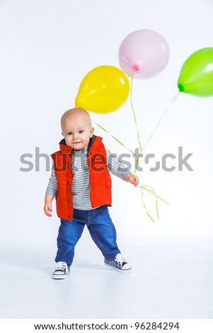 Cute funny little boy in a red vest with colored balloons. In the studio