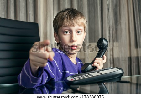 Cute funny little boy pretending to be a boss in an office asking to make a phone call  - stock photo