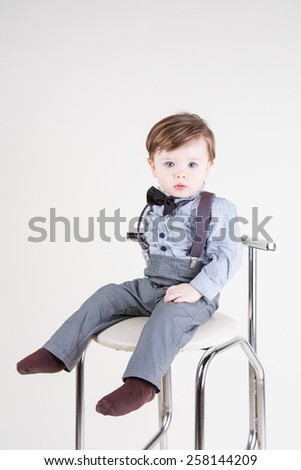 Cute funny little boy sitting on a chair and smiling - stock photo
