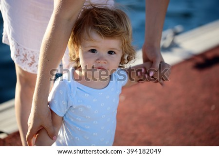 Cute funny little child boy with blonde hait in shirt standing with mother holding hands outdoor sunny day looking forward, horizontal picture - stock photo