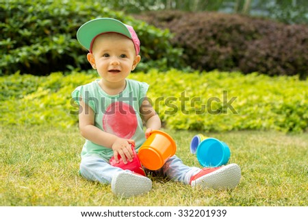 Cute funny little girl baby toddler playing with cups in green garden hat  - stock photo