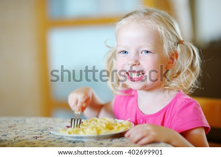 Cute funny little girl eating spaghetti at home - stock photo