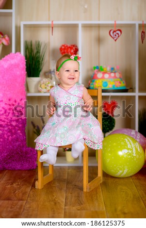 Cute funny little kid have a fun with colored balloons in the bright room  laughing  - stock photo