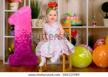 Cute funny little kid in first birthday with colored balloons in the bright room on the chair  - stock photo