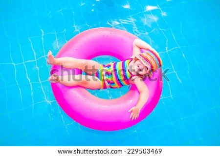 Cute funny little toddler girl in a colorful swimming suit and hat relaxing on an inflatable toy ring floating in a pool having fun during summer vacation in a tropical resort - stock photo