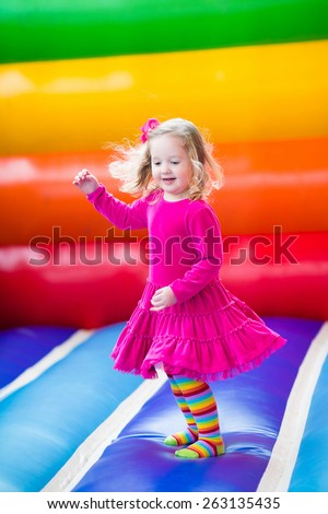 Cute funny preschool little girl in a colorful dress playing, jumping and bouncing in an inflatable castle having fun at a children birthday party on a kids playground in summer - stock photo