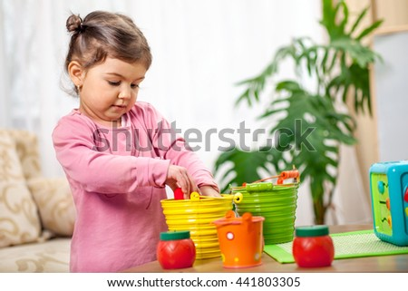 Cute funny preschooler little girl  playing with toys in room, Children at day care - stock photo