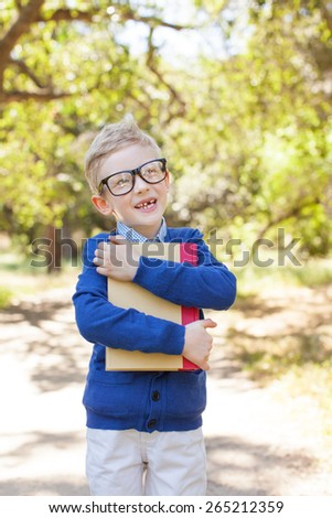 cute funny schoolboy in glasses holding book ready to go to school, back to school concept