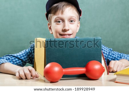 Cute funny schoolboy sitting in classroom with colorful books and a dumbbell smiling (healthy learning concept)  - stock photo