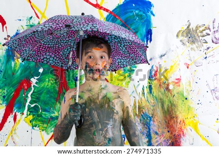 Cute funny shirtless little boy covered in fresh paint standing under an umbrella in front of his vibrant colorful contemporary artwork looking at the camera with an astonished look - stock photo