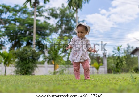 Cute funny smiling baby making her first steps in a sunny summer garden