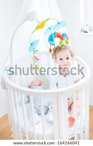 Cute Funny Toddler Girl Sitting In A Crib Of Her Her