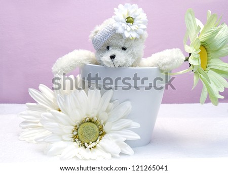 Cute generic white bear sitting in white planter with over-sized large daisies surrounding it with pink background - with transparent fairy wings - stock photo