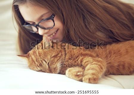 Cute ginger cat sleeps near kid girl on the sofa - stock photo