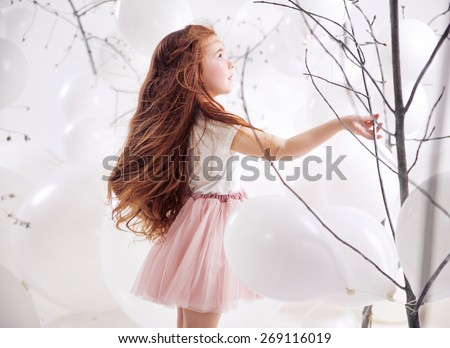 Cute ginger girl playing with balloons - stock photo