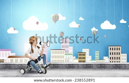 Cute girl against drawn background riding three wheeled bike - stock photo