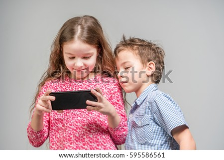 Cute girl and boy looking into the phone on a gray background. Isolated