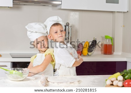 Cute girl and boy proud to wear chef uniform while baking in the kitchen, posing back to back with folded arms
