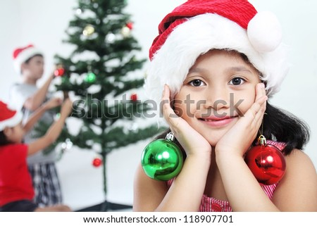Cute girl and children decorating a christmas tree. - stock photo