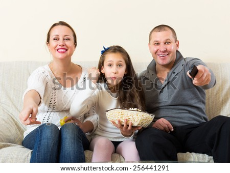 Cute girl and happy parent sitting with popcorn in front of TV - stock photo