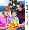 Cute girl and her mother and grandmother watching Christmas gifts - stock