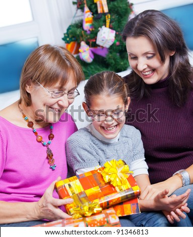 Cute girl and her mother and grandmother watching Christmas gifts - stock photo