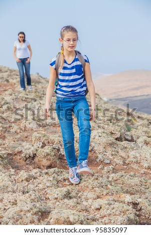 Cute girl and her mother hiking in the cross-country - stock photo