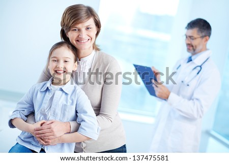 Cute girl and her mother looking at camera with doctor working on background - stock photo