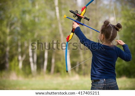 Cute girl archer with bow shooting in sunny summer day. little girl shoots bow in the park. Outdoors. Sport activities with children.  - stock photo