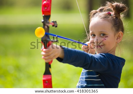 Cute girl archer with bow shooting in sunny summer day. little girl shoots bow in the park. Outdoors. Sport activities with children. Sport and lifestyle concept. Aiming high - stock photo