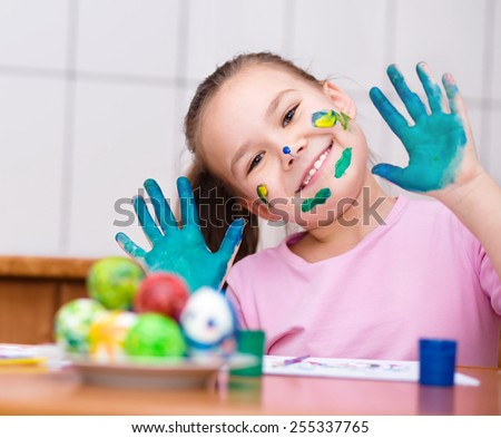 Cute girl are coloring eggs for Easter - stock photo