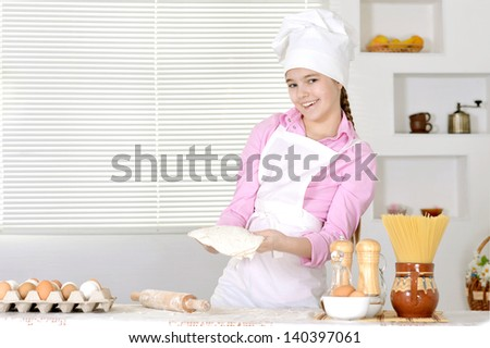 Cute girl baking cake in the kitchen at home