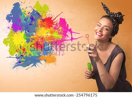 Cute girl blowing bubble spalsh graffiti into wall - stock photo
